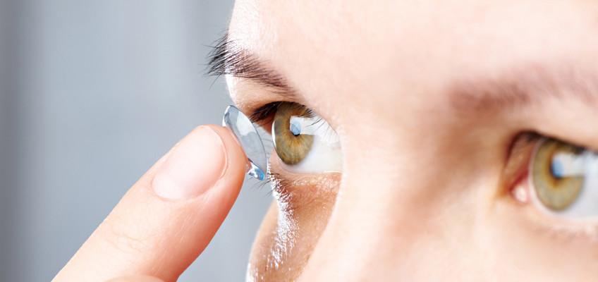Woman puts contact lens