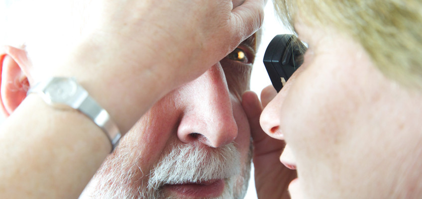 Doctor undertaking an eye examination with an opthalmoscope