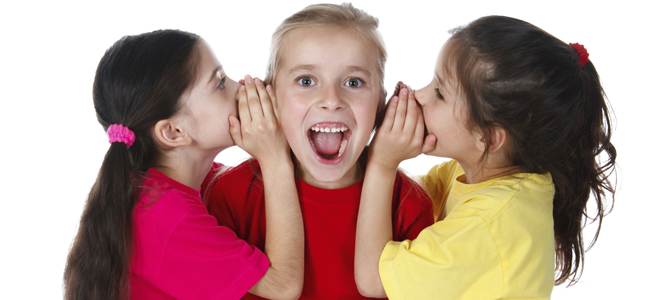Two girls whispering something to third girl